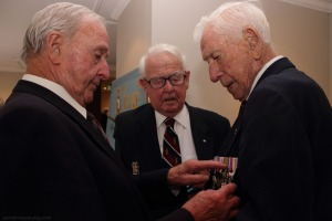 Hugh McLeod points out something on Don Huxtable's medals to Don Southwell